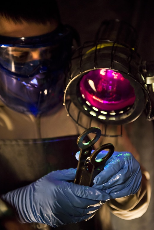 Airman 1st Class Landen Johnston, 5th Maintenance Squadron non-destructive inspection apprentice, performs a magnetic particle inspection under an ultraviolet light at Minot Air Force Base, N.D., Oct. 18, 2016. The fluorescing particles under ultraviolet light allow Airmen to easily locate cracks and imperfections on magnetized aircraft parts. (U.S. Air Force photo/Airman 1st Class J.T. Armstrong)