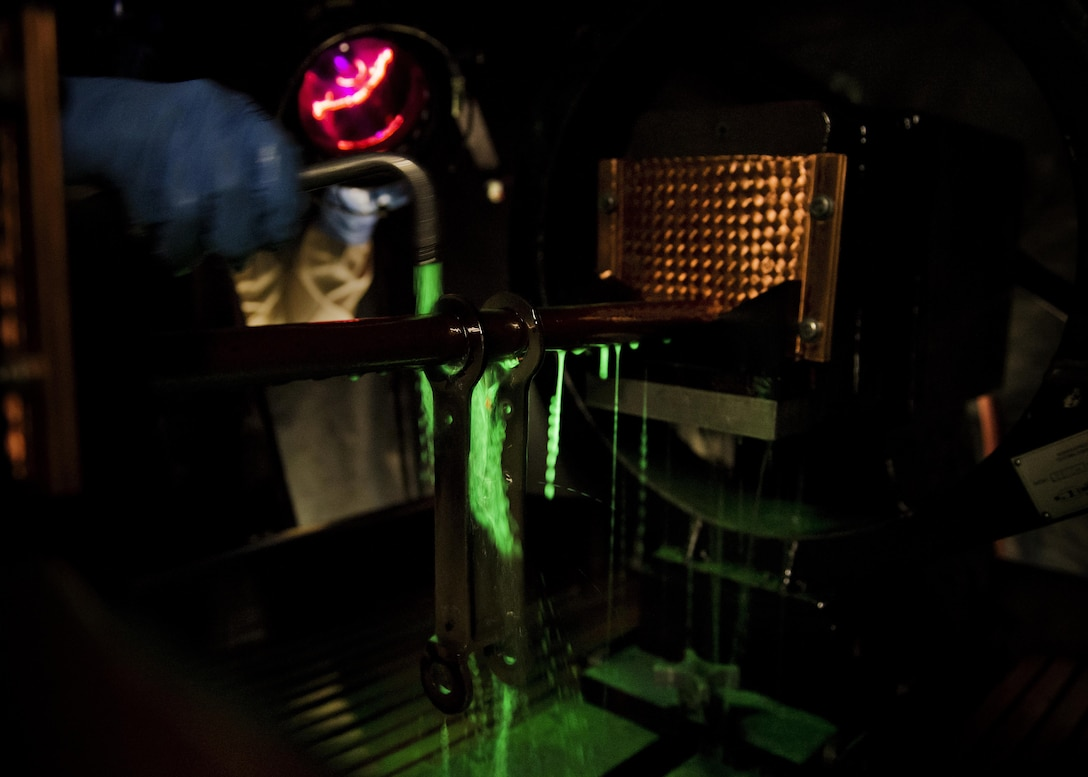 Airman 1st Class Landen Johnston, 5th Maintenance Squadron non-destructive inspection apprentice, coats a magnetized aircraft piece under an ultraviolet light at Minot Air Force Base, N.D., Oct. 18, 2016. The fluorescing particles under ultraviolet light allow Airmen to easily locate cracks and imperfections on magnetized aircraft parts. (U.S. Air Force photo/Airman 1st Class J.T. Armstrong)