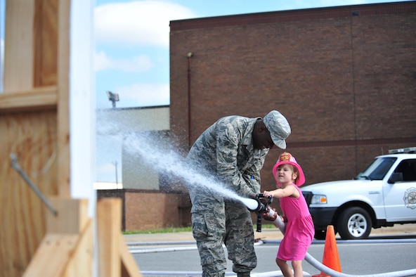 A firefighter assigned to the 509th Civil Engineer Squadron assist a Whiteman youth in using a fireman's hose to demonstrate firefighting techniques. The fire prevention week finale gave participants an opportunity to see firsthand techniques used by Whiteman firefighters. (U.S. Air Force photo by Senior Airman Jovan Banks)
