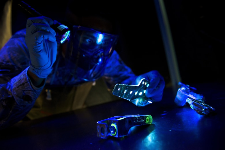 Airman 1st Class Alexander Shaikh, 5th Maintenance Squadron non-destructive inspection journeyman, shines a black light during a fluorescent penetrant inspection at Minot Air Force Base, N.D., Oct. 18, 2016. The black light aids Shaikh in locating cracks and imperfections on parts of the B-52H Stratofortress and aircraft support equipment. (U.S. Air Force photo/Airman 1st Class J.T. Armstrong)