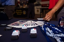 An attendee picks up a business card during a job fair hosted by the Georgia Department of Labor and Moody's Airman and Family Readiness Center, Oct. 20, 2016, at Moody Air Force Base, Ga. For individuals who want to enhance their employment chances, the base Airman and Family Readiness Center's Transition Assistance Programs offer resources to build resumes and improve presentation and networking skills. (U.S. Air Force photo by Airman 1st Class Greg Nash)