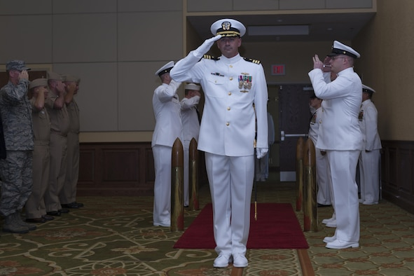 U.S. Navy Cmdr. Timothy Knapp, incoming Center for Naval Aviation Technical Training Unit Keesler commanding officer, renders a salute as he enters the CNATTU Keesler change of command ceremony at the Bay Breeze Event Center Oct. 20, 2016, on Keesler Air Force Base, Miss. Knapp was previously the executive officer at the Fleet Weather Center, Norfolk, Va. (U.S. Air Force photo by Andre' Askew/Released)