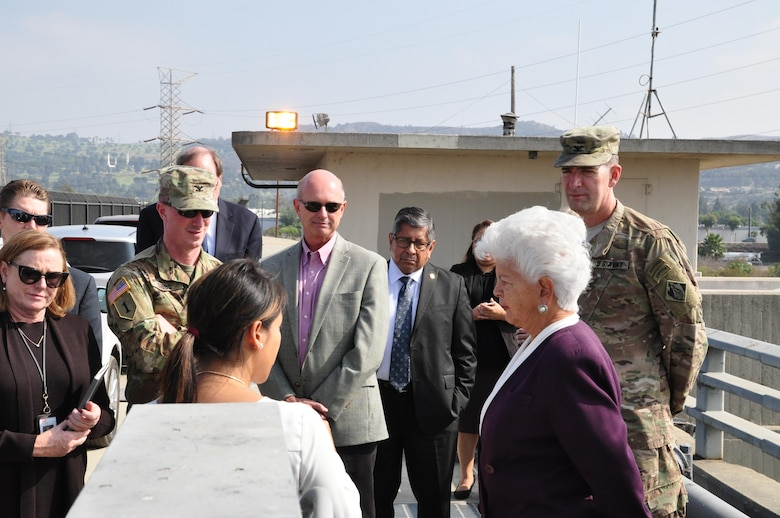 Lillian Doherty (center foreground), chief of Operations Division, briefs Rep. Grace Napolitano on the operation of control gates along the San Gabriel River side of Whittier Narrows Dam during Col. Helmlinger's October 12 visit to the dam. Concerns about premature opening of the gates under certain conditions are a factor in the dam's recently increased safety classification.