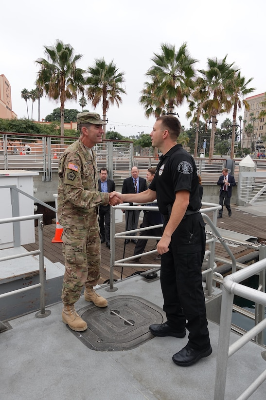 Oct. 14, Los Angeles Port Police Officer, Michael Glimpse, greets South Pacific Division Commander Col. Peter Helmlinger, as he boards the police dive boat for his tour of the Port of Los Angeles.