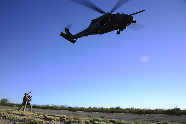 Pararescuemen assigned to the 48th Rescue Squadron signal to an Airman in an HH-60G Pave Hawk during alternate insertion/extraction training at Davis-Monthan Air Force Base, Ariz., Oct. 18, 2016. The Airmen are required to perform AIE training every year and do multiple iterations throughout the year to maintain proficiency in all the methods. (U.S. Air Force photo by Senior Airman Betty R. Chevalier)
