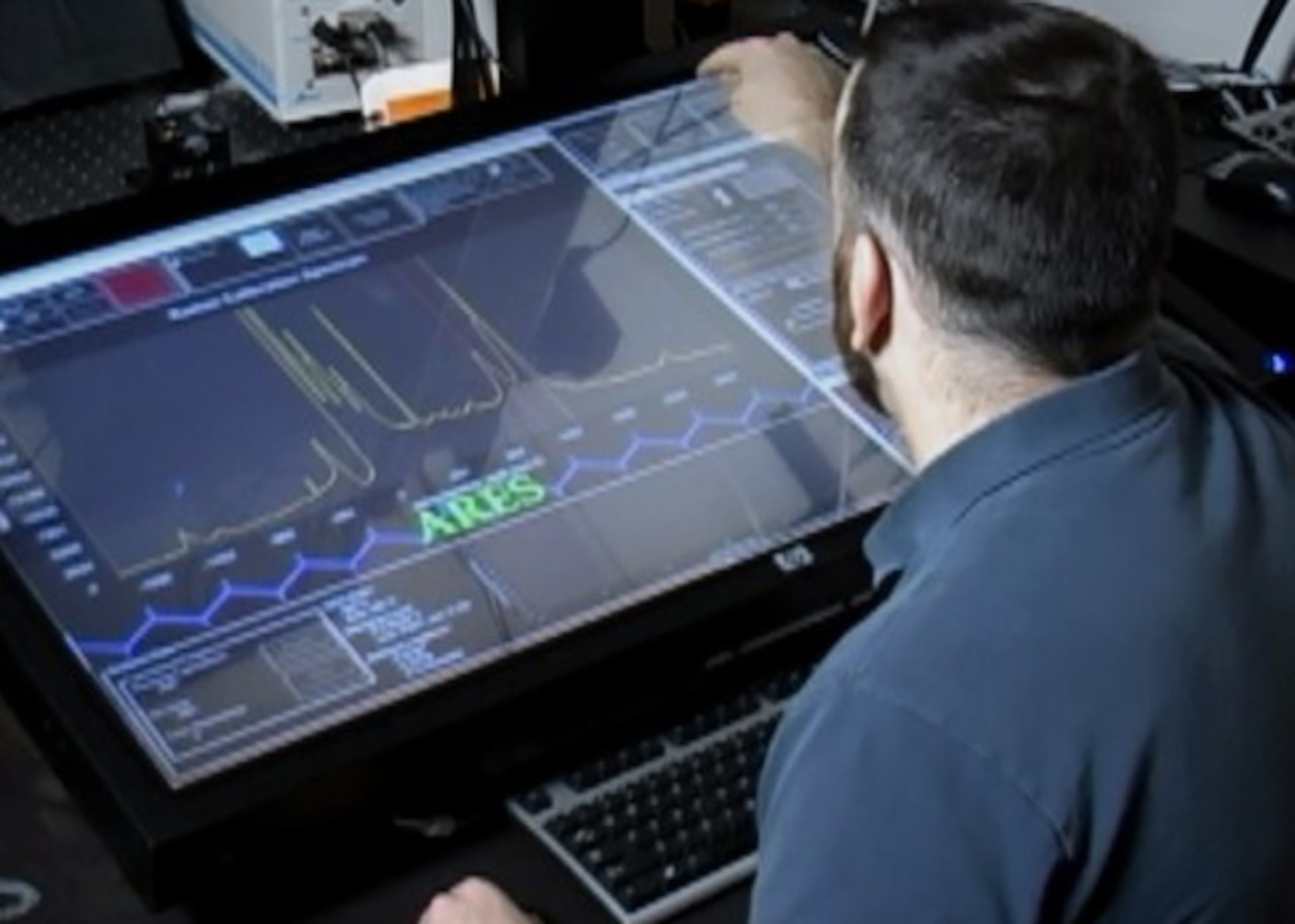 A materials researcher examines experimental data on the ARES artificial intelligence planner. The ARES Autonomous Research System, developed by the Air Force Research Laboratory, uses artificial intelligence to design, execute and analyze experiments at a faster pace than traditional scientific research methods. (Courtesy Photo)
