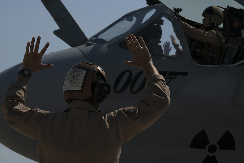 U.S. Marine Corps Cpl. Kogut Bradley, Tactical Electronic Warfare Squadron 4 plane captain, signals for hands up at Incirlik Air Base, Turkey, Sept. 16, 2016. Hands up is one of many hand signals used by plane captains and means ordnances are being armed. (U.S. Air Force photo by Staff Sgt. Ciara Gosier)