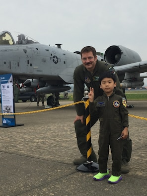 Capt. Daniel Hann, 25th Fighter Squadron pilot, poses with a Korean boy at the Sacheon Airshow at Sacheon Base, Republic of Korea, Oct. 20, 2016. 7th Air Force provided both an F-16 and A-10 Thunderbolt II static display for the four-day airshow, showcasing U.S. Air Force capabilities to over 260,000 attendees. (U.S. Air Force photo by 1st Lt. Lauren Linscott/Released)