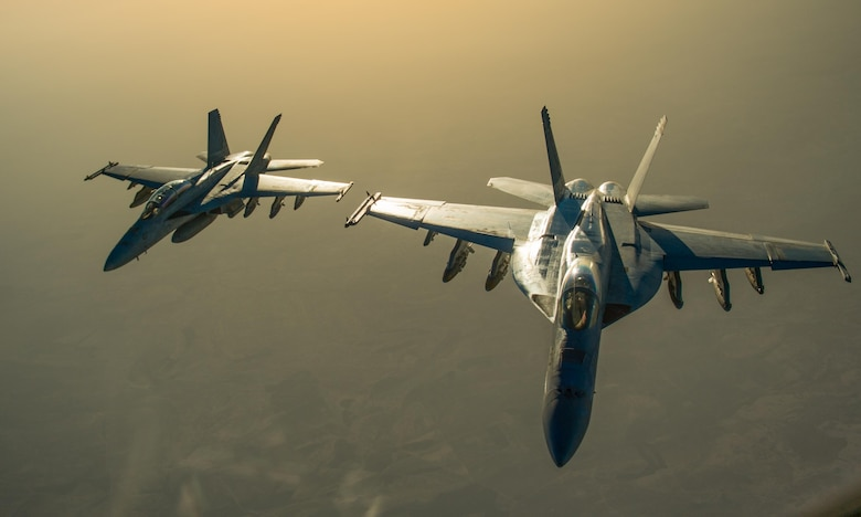 Two U.S. Navy F/A-18 Super Hornets fly in formation after receiving fuel from a KC-135 Stratotanker over Iraq in support of Operation Inherent Resolve Oct 17, 2016. The operational mission of Operation Inherent Resolve is to militarily defeat Da'esh in the Combined Joint Operation Area in order to enable whole-of-coalition governmental actions to increase regional stability.(U.S. Air Force photo by Staff Sgt. Douglas Ellis/Released)
