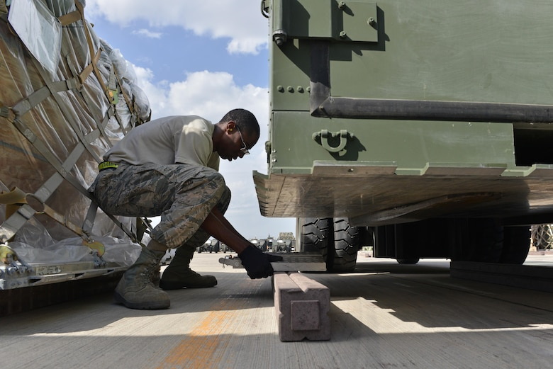 U.S. Air Force Airman 1st Class Josiah Purnell, 728th Air Mobility Squadron air transportation journeyman, places a scale underneath cargo Oct. 18, 2016, at Incirlik Air Base, Turkey. While inspecting cargo, air transportation specialists validate cargo weight and document accordingly. (U.S. Air Force photo by Senior Airman John Nieves Camacho)