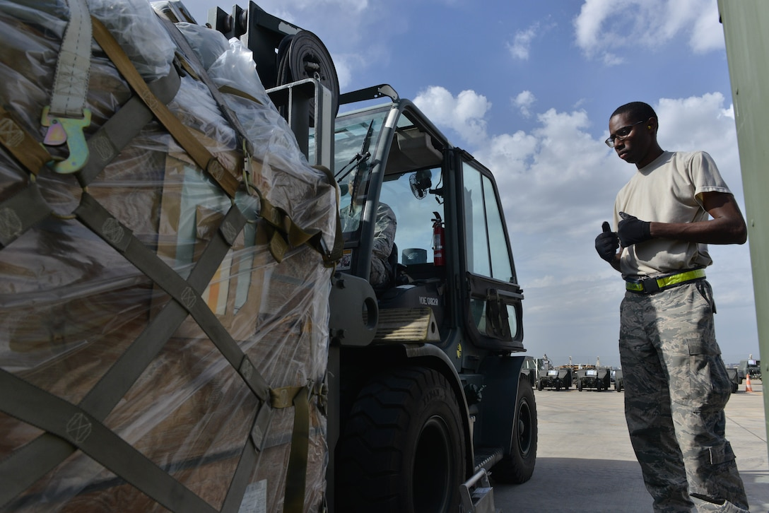 U.S. Air Force Airman Kyle George (left), 728th Air Mobility Squadron (AMS) air transportation journeyman, lifts cargo with a 10K forklift as Airman 1st Class Josiah Purnell, 728th AMS air transportation journeyman, spots him Oct. 18, 2016, at Incirlik Air Base, Turkey. The cargo contained A-10 Thunderbolt II support equipment that aids combat operations for Operation INHERENT RESOLVE. (U.S. Air Force photo by Senior Airman John Nieves Camacho)
