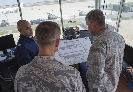 Capt. Trevor Boyd, 89th operations Support Squadron's Airfield Operations Flight commander, duscusses future plans for the Joint Base Andrews flightlint to Chief Master Sgt. Todd Petzel (center) 18th Air Force command chief, and Lt. Gen. Sam Cox (right), 18th AF commander, on JBA, Md., Oct. 19, 2016. During his visit of the 89th Airlift Wing, Cox toured flight planning, weather and the airfield. (U.S. Air Force photo/Senior Airman Ryan J. Sonnier/Released)