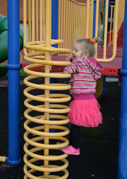 Aliya Sokora, 3, daughter of U.S. Air Force Lt. Col. Brandon Sokora, 100th Civil Engineer Squadron commander, pulls herself up on playground equipment as she plays Oct. 19, 2016, on RAF Mildenhall, England. Aliya was born a congenital amputee, without her left lower arm. October is National Disability Employment Awareness month and the 100th CES commander shared his family's story at a lunch celebrating the many varied contributions of America's workers with disabilities. (U.S. Air Force photo by Karen Abeyasekere)