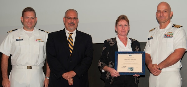 Michelle Turner receives her certificate of appreciation from Naval Surface Warfare Center Dahlgren Division (NSWCDD) Technical Director John Fiore, NSWCDD Commanding Officer Capt. Brian Durant, right, and Combat Direction Systems Activity Dam Neck Commanding Officer Cmdr. Andrew Hoffman at the 2016 NSWCDD academic awards ceremony. Turner was recognized for completing her system safety certification from the University of Southern California, and commended for her commitment to personal and professional development.