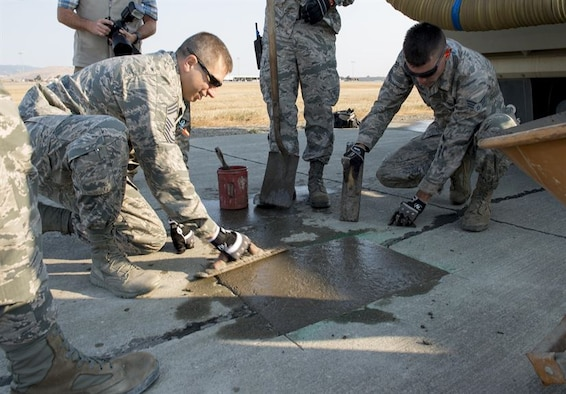 A concrete taxiway repair is completed by Airmen assigned to the 60th Air Mobility Wing at Travis Air Force Base, Calif., Aug. 19, 2016. Using similar techniques on a much larger scale in 2016, members of the 1st Expeditionary Civil Engineer Group repaired runway damage caused by Islamic State of Iraq and the Levant at Qayyarah West Airbase in northern Iraq's Ninawa province. (U.S. Air Force photo/Heide Couch)