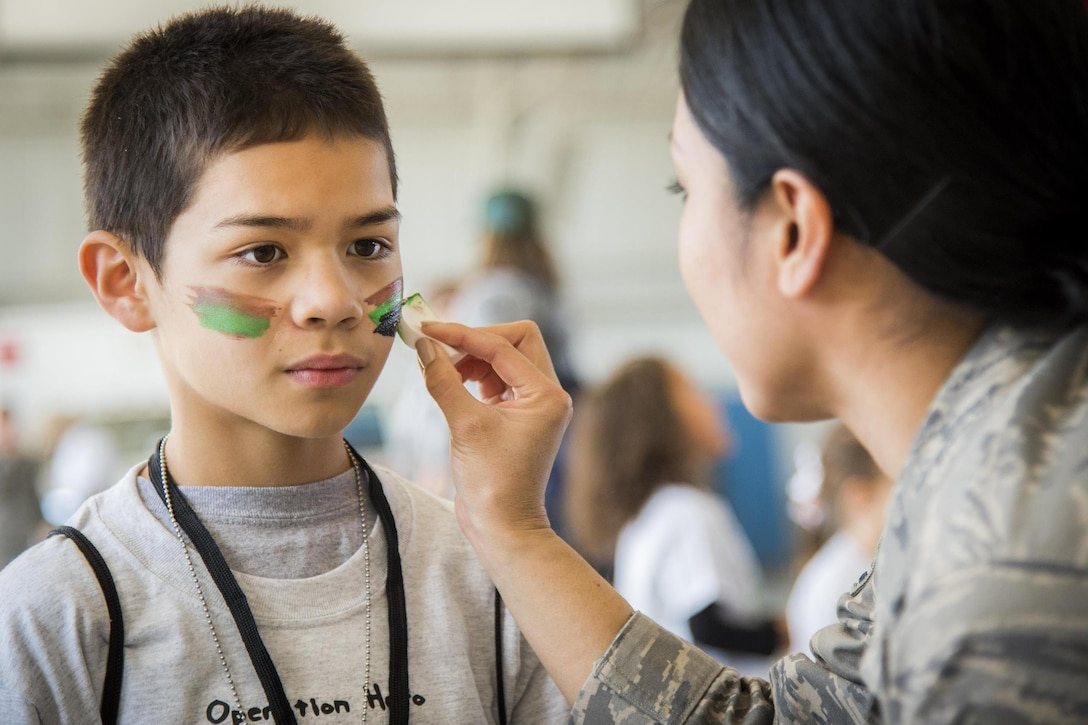 An airman paints a child's face during