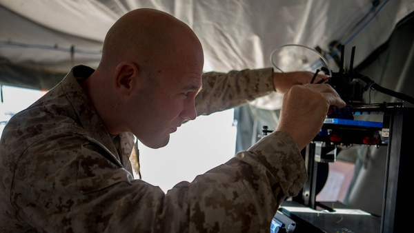 U.S. Marine Corps Chief Warrant Officer 2 Mathew Wright, a motor transportation maintenance officer with Marine Wing Support Squadron 372, conducts maintenance on an Invent3D printer during a 3-D printer integration exercise at site 50 training area, Wellton, Arizona, Oct. 18, 2016. Wright used the additive manufacturing equipment to make objects from 3-D model data throughout Weapons Tactics Instructors course 1-17.  Marine Aviation Weapons and Tactics Squadron One cadre host WTI which emphasizes operational integration of the six functions of Marine Corps aviation in support of a Marine Air Ground Task Force. MAWTS-1 provides standardized advanced tactical training and certification of unit instructor qualifications to support Marine aviation Training and Readiness and assists in developing and employing aviation weapons and tactics.