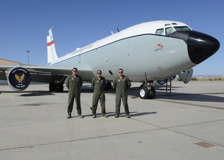 From left to right: Master Sgt. Aaron Ray, Senior Master Sgt. Scott Scurlock, and Tech. Sgt. Colin Wernecke of the 370th Flight Test Squadron pose for a photo in front of a KC-135 Stratotanker test aircraft. (U.S. Air Force photo by Kenji Thuloweit)