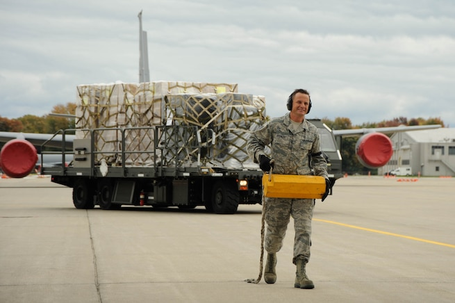 Staff Sgt. William Spencer moves a chock block during the loading process of a C-130 Hercules at Selfridge Air National Guard Base, Mich., Oct. 21, 2016. Spencer is a member of the 127th Logistics Readiness Squadron at the base. The aircraft is from the 302nd Airlift Wing, Peterson Air Force Base, Colo. The Air Force personnel were loading a supply of rice and soy-based meals, created by the Michigan-based charity Kids Against Hunger, for shipment to Guatemala. U.S. law allows military assets to be used to ship humanitarian supplies internationally under certain criteria. (U.S. Air National Guard photo by John Brandenburg)