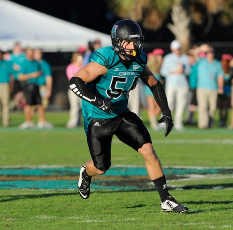 Second Lieutenant Tyler R. Watkins defends his zone as Coastal Carolina University's linebacker during the final game of the regular season, facing off against Charleston Southern University at Brooks Stadium, Conway, S.C., Oct. 25, 2014. Watkins applied everything he learned playing football to his training at Officer Candidates School aboard Marine Corps Base Quantico, Va. He graduated OCS with Officer Candidate Class 222, which had the most OCS graduates since 2009, on Aug. 6, 2016. Due to injuries sustained during OCS, he is temporarily assigned to the Plans and Research section at Marine Corps Recruiting Command aboard MCB Quantico. Watkins hopes to return to training in March 2017.
