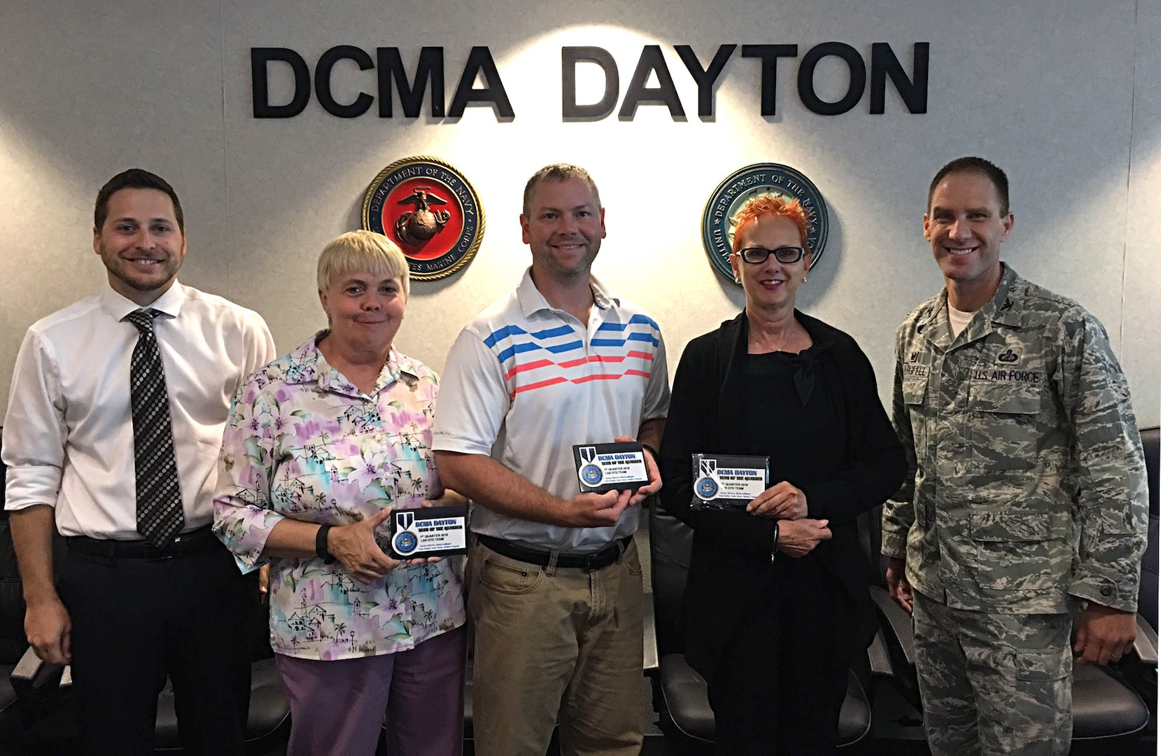 Defense Contract Management Agency Dayton on-time delivery improvement team members Mathew Duguid, Norma Shreves, Gabe Stone and Pam Batlak are honored as Dayton's team of the quarter by their commander, Air Force Col. Eric Obergfell. The team was celebrated for their continuous process improvement efforts. As the team lead, Duguid had the plaques made for his team as a thank you for their hard work. (DCMA photo by Jason Edem)