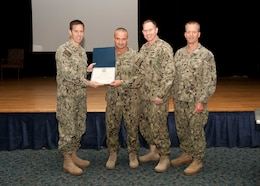 Chief Petty Officer Michael Hancock, center, receives a letter of appreciation for his work and command coordination efforts in the 2016 Navy-Marine Corps Relief Society fundraising drive at the multipurpose room aboard Naval Support Activity Bahrain, Oct. 23, 2016. The Navy-Marine Corps Relief Society is to provide emergency financial assistance to active duty and retired Navy and Marine Corps personnel and their families.