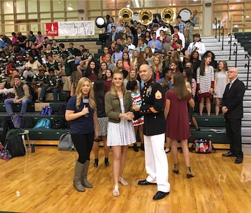 Staff Sgt. Clifford M. Lucker presents Carol Turner with the March to Greatness challenge coine during the live airing of the pep rally Oct. 21, 2016, at River Bluff High School in Lexington, South Carolina.   Turner, a snare drum player and band president, earned the recognition for the hard work and dedication she shows during marching band and in her community. Lucker is a canvassing recruiter at Marine Corps Recruiting Station Columbia. (Official Marine Corps photo by Sgt. Tabitha Bartley/Released)