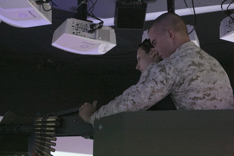 Lance Cpl. Brian Powell, team leader, 1st Battalion, 7th Marine Regiment, shows his wife, Stacy, how to utilize an M2 Browning .50 caliber machine gun, in the Combat Convoy Simulator at Camp Wilson aboard Marine Corps Air Ground Combat Center, Twentynine Palm, Calif., Oct. 14, 2016. (Official Marine Corps photo by Cpl. Thomas Mudd/Released)