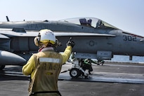 Navy Petty Officer 3rd Class Gabrielle Embry signals to an F/A-18F Super Hornet on the flight deck of the aircraft carrier USS Dwight D. Eisenhower in the Persian Gulf, Oct. 20, 2016. The pilot and aircraft are assigned to Strike Fighter Squadron 131. Embry is an aviation boatswain's mate. Navy photo by Petty Officer 3rd Class Nathan T. Beard