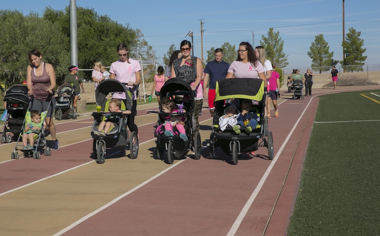 Marine Corps Air Ground Combat Center patrons walk around the track with their children during the Officers' Spouses' Club third annual Pink Breast Cancer Awareness Walk at Felix Field aboard the Marine Corps Air Ground Combat Center, Twentynine Palms, Calif., Oct. 14, 2016. OSC hosted the walk to raise awareness and money for breast cancer research. (Official Marine Corps photo by Lance Cpl. Dave Flores/Released)