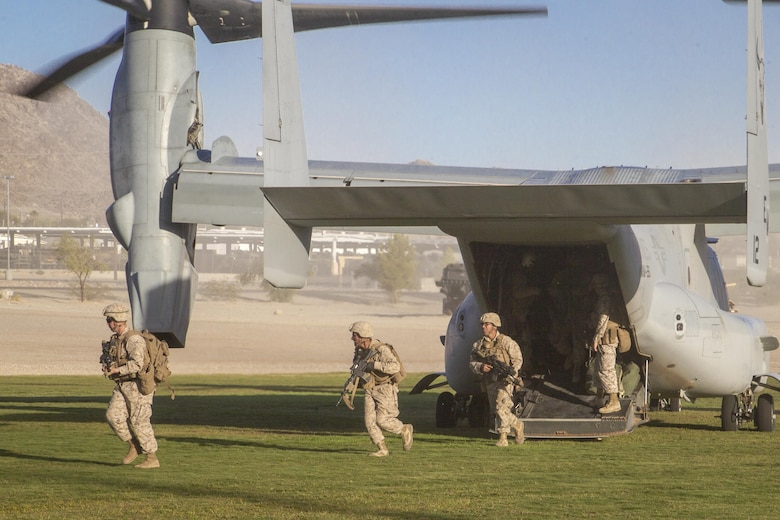 """Marines with 2nd Battalion, 3rd Marine Regiment, exit an MV-22 """"Osprey"""" during a Non-combatant Evacuation Operation exercise aboard Marine Corps Air Ground Combat Center, Twentynine Palms, Calif., Oct. 14, 2016. (Official Marine Corps photo by Cpl. Connor Hancock/Released)"""