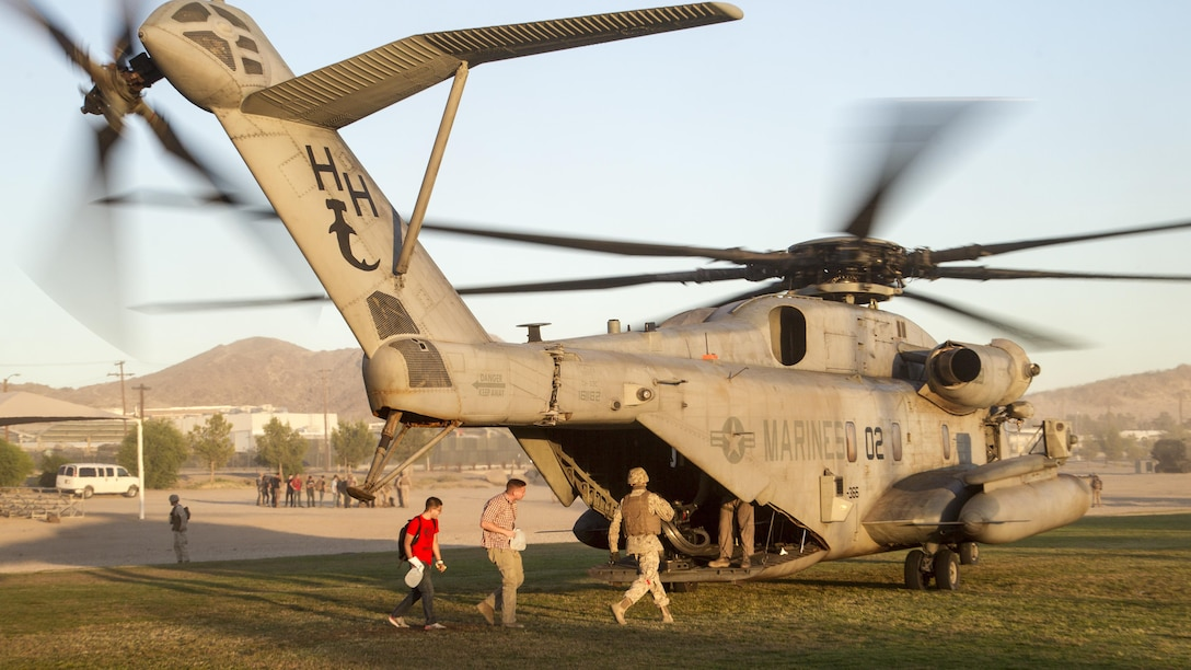 """Marines with 2nd Battalion, 3rd Marine Regiment, escort simulated evacuees into a CH-53 """"Super Stallion"""" landing zone during a Non-combatant Evacuation Operation exercise aboard Marine Corps Air Ground Combat Center, Twentynine Palms, Calif., Oct. 14, 2016. (Official Marine Corps photo by Cpl. Connor Hancock/Released)"""