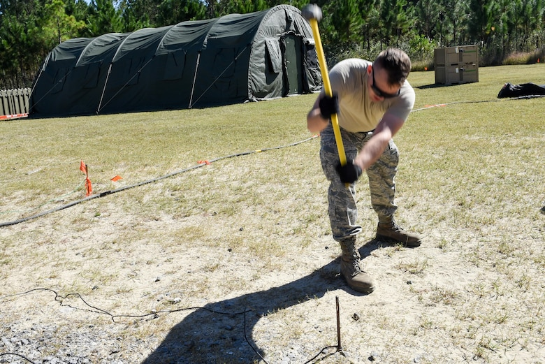 An Air Commando with the 1st Special Operations Civil Engineer Squadron, hammers a grounding rod in the ground during the construction of a Joint Special Operations Air Detachment at the Gulfport-Biloxi International Airport in Gulfport, Miss., Oct. 22, 2016. The 1st Special Operations Wing is participating in Exercise Southern Strike to practice tactical skills and test the capabilities of its Airmen and assets in a deployed environment. (U.S. Air Force photo by Senior Airman Jeff Parkinson)