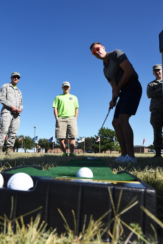 U.S. Air Force Senior Airman Alex Harris, 17th Contracting Squadron contract administrator, sinks a putt during the Make Goodfellow Great Trucktoberfest event at the parade grounds on Goodfellow Air Force Base, Texas, Oct. 21, 2016. Golfing is one of the clubs offered at Goodfellow. (U.S. Air Force photo by Senior Airman Joshua Edwards/Released)