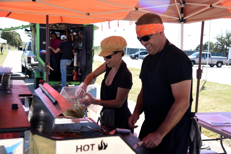 U.S. Air Force Master Sgt. Blake Ferguson, 17th Force Supoort Squadron airmen leadership school commandant, and Marla Ferguson, food vendor, cook Korean tacos during the Make Goodfellow Great Trucktoberfest event at the parade grounds on Goodfellow Air Force Base, Texas, Oct. 21, 2016. Trucktoberfest was an initiative to get individuals interested in joining Goodfellow clubs. (U.S. Air Force photo by Senior Airman Joshua Edwards/Released)