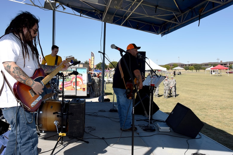 The Back Road Trubadors play for the Make Goodfellow Great Trucktoberfest event at the parade grounds on Goodfellow Air Force Base, Texas, Oct. 21, 2016. During Trucktoberfest, individuals could sign up for a Goodfellow club or get food from various local food truck vendors. (U.S. Air Force photo by Senior Airman Joshua Edwards/Released)