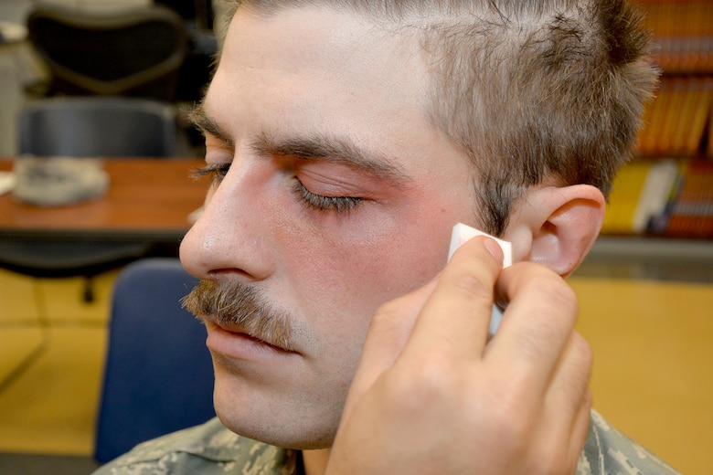 U.S. Air Force Staff Sgt. Ryan Hacker, 17th Communications Squadron software engineer supervisor, has moulage applied to his face during the Black Eye Campaign at Goodfellow Air Force Base, Texas, Oct. 21, 2016. Participants who received a black eye were told to act reserved and try not to bring attention to themselves. (U.S. Air Force photo by Airman 1st Class Randall Moose/Released)