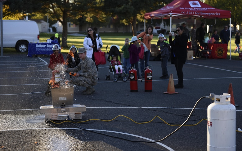 A 92nd Civil Engineer Squadron firefighter holds live, fire extinguisher training as part of the Fire Prevention Week Carnival Oct. 12, 2016, at Fairchild Air Force Base. The 92nd CES Fire Department staff used the event to teach children fire safety habits, from crawling through a simulated fire to getting hands-on training using a fire extinguisher and hose. (U.S. Air Force photo/Airman 1st Class Sean Campbell)