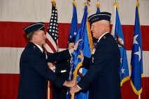 From left, Air Force Chief of Staff Gen. David L. Goldfein passes the guidon of Air Force Space Command, to Gen. John Raymond at Peterson Air Force Base, Colo., Oct. 25, 2016. Raymond was previously the Deputy Chief of Staff for Operations, Headquarters Air Force. (U.S. Air Force Photo/Craig Denton)