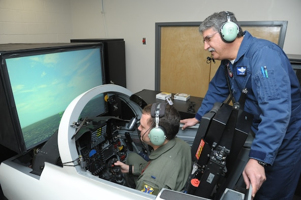 First Lt. Austin Hornsby,435th Flying Training Squadron student pilot trains on a simulator, while Jose Colon, instructor looks on, at Joint Base San Antonio-Randolph, Oct. 20, 2016. 	The simulator accomplishes less complex missions, such as instrument and emergency procedures training, due to the limited visual representation compared with the simulators known as the operational flight trainer and the weapon systems trainer.