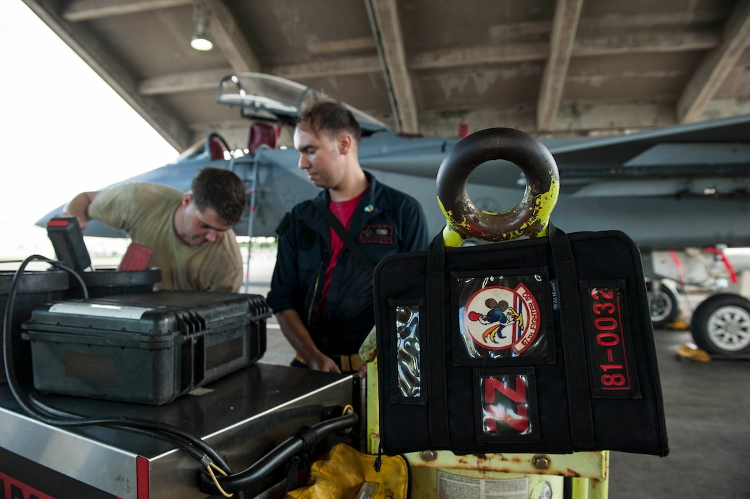 U.S. Air Force Staff Sgt. Carl Petmecky and Senior Airman Alexander Reyes, 67th Aircraft Maintenance Unit crew chiefs, secure tools and equipment during a shift change Oct. 21, 2016, at Kadena Air Base, Japan. Petmecky and Reyes performed maintenance on an F-15 Eagle undergoing an engine swap. (U.S. Air Force photo by Senior Airman Peter Reft/Released)