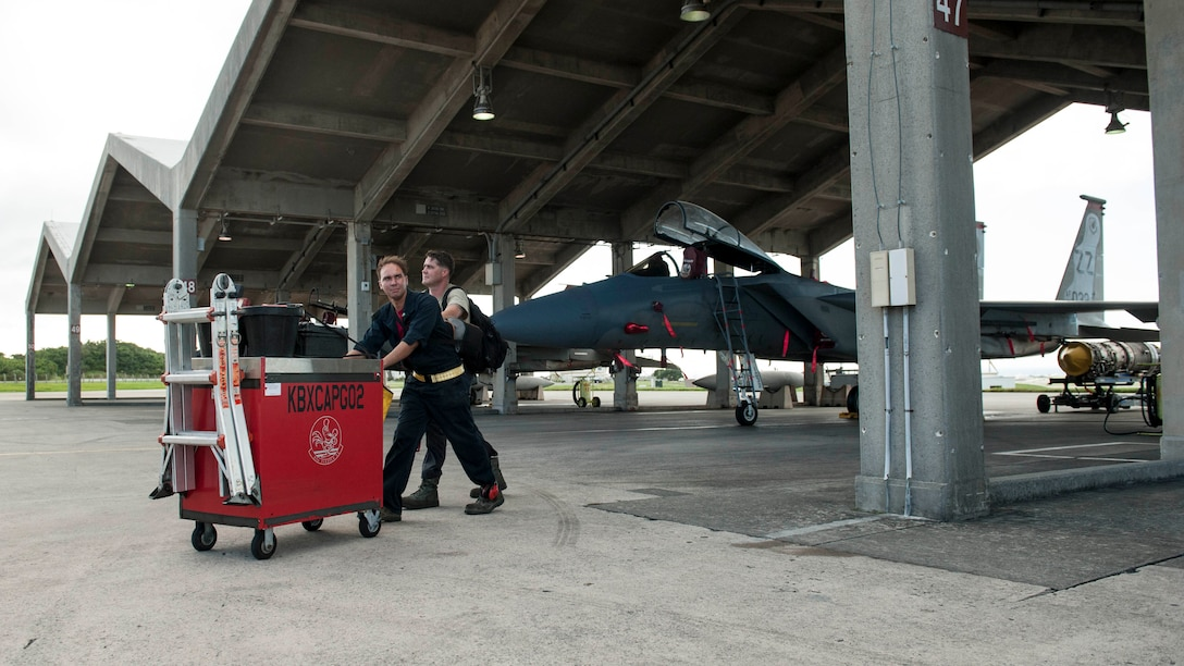 U.S. Air Force Staff Sgt. Carl Petmecky and Senior Airman Alexander Reyes, 67th Aircraft Maintenance Unit crew chiefs, push their tool cart off the flightline during a shift change Oct. 21, 2016, at Kadena Air Base, Japan. Petmecky and Reyes performed maintenance on an F-15 Eagle, an operation that utilizes 24-hour manning to ensure constant mission readiness should the call of duty arise to defend Okinawa and other U.S. interests in the Indo-Asia Pacific region. (U.S. Air Force photo by Senior Airman Peter Reft/Released)