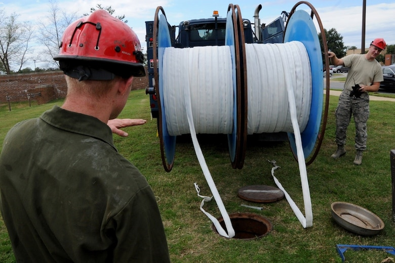 Senior Airman Cameron Porter and Airman First Class Michael Eckhoff, 744th Communications Squadron cable antenna maintenance, lower inner duct fabric for running 1,600 feet of fiber optic cable to the flight line on Joint Base Andrews Oct. 13, 2016. The 744th CS delivers many cyberspace operations such as secure networks, voice communications services, and communications infrastructure and intrusion detection systems within the National Capital Region.  (U.S Air Force photo/Tech. Sgt. Matt Davis)
