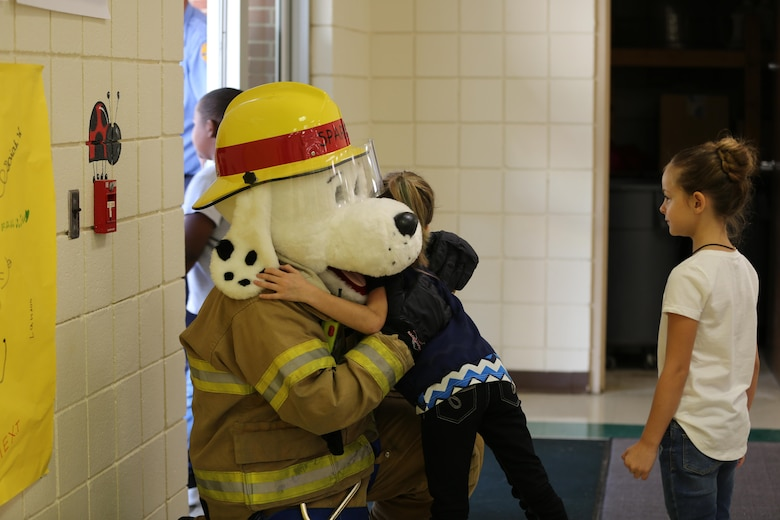 Sparky the Fire Dog hugs a student at W.J. Gurganus Elementary School in Havelock, N.C., Oct. 20, 2016. The Cherry Point Fire and Emergency Services Department visited the school to demonstrate what to do in fire emergencies and how to prevent them. The students also learned about the equipment firefighters use every day to complete their mission. Sparky is the mascot for the Cherry Point Fire and Emergency Services Department. (U.S. Marine Corps photo by Lance Cpl. Mackenzie Gibson/Released)