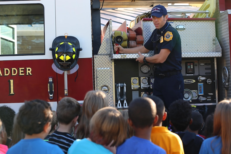 Edward Hudson explains the functions of a ladder truck to students at W.J. Gurganus Elementary School in Havelock, N.C., Oct. 20, 2016. The Cherry Point Fire and Emergency Services Department visited the school to demonstrate what to do in fire emergencies and how to prevent them. The students also learned about the equipment firefighters use every day to complete their mission. Hudson is the fire captain with the Cherry Point Fire and Emergency Services Department. (U.S. Marine Corps photo by Lance Cpl. Mackenzie Gibson/Released)
