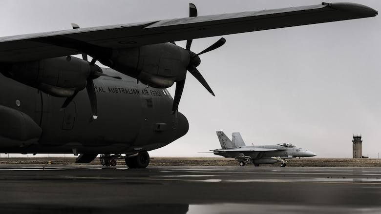 A Navy F-18 from Naval Air Station Oceana, Virginia, passes under the wings of a Royal Australian Air Force C-130J at Mountain  Home Air Force Base, Idaho, Oct. 23, 2016. Units from across the world visit the base to use its extensive training ranges. (U.S. Air Force photo by Senior Airman Connor J. Marth/Released)
