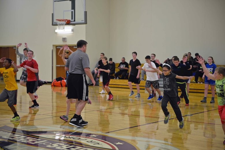 Troy Pearson, director of the Minnesota Timberwolves and Lynx Academy, conducts warm up drills at the military kids basketball camp Oct. 22.