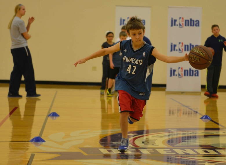 Stephanie Sension (left) conducts ball handling drills at the military kids basketball clinic Oct. 22.