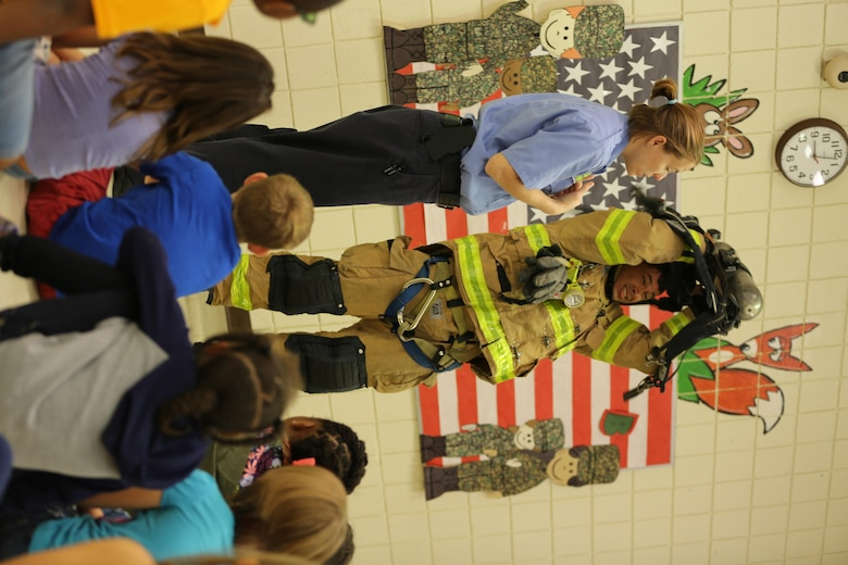 Brandee Ridgway (left) explains how fire safety equipment works as Raymond Bane dons his firefighting gear at W.J. Gurganus Elementary School in Havelock, N.C., Oct. 20, 2016. The Cherry Point Fire and Emergency Services Department visited the school to demonstrate what to do in fire emergencies and how to prevent them. The students also learned about the equipment firefighters use every day to complete their mission. Ridgway is a fire inspector, and Bane is a firefighter with the Cherry Point Fire and Emergency Services Department. (U.S. Marine Corps photo by Lance Cpl. Mackenzie Gibson/Released)