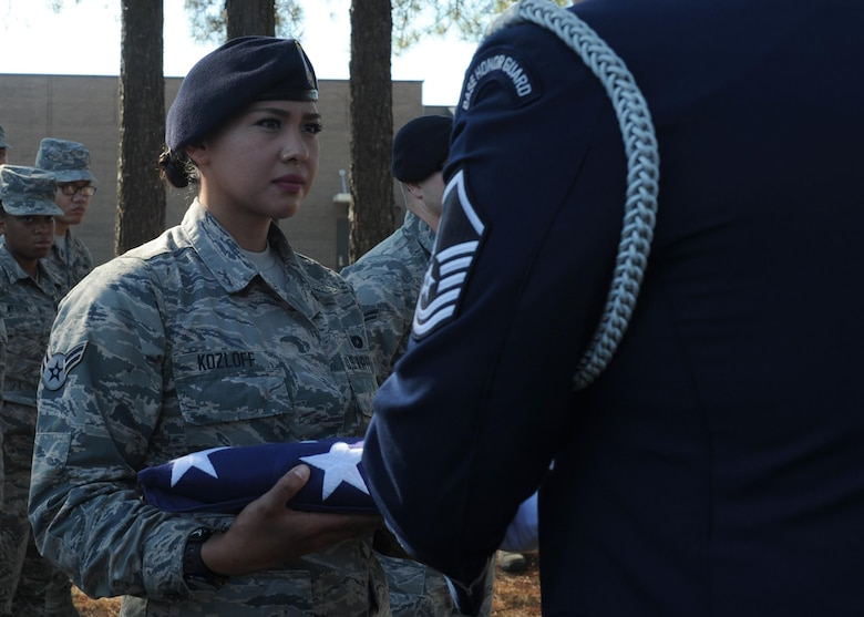 U.S. Air Force Airman 1st Class Sasha Kozloff, 19th Security Forces Squadron Defender, accepts a flag during an Honor Guard demonstration as part of the First Term Airman's Class Oct. 6, 2016. Team Little Rock's Honor Guard demonstrated proper funeral procedures at the bi-monthly FTAC class to recruit Airmen. (U.S. Air Force photo by Airman Grace Nichols)